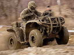 A man covered in mud, driving a quad bike