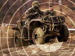 A faded image of a sniper target on an image of a man driving a quad bike through a muddy field
