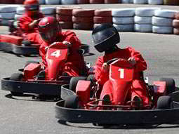 A line of three people in red karts and racing suits, driving on an outdoor track