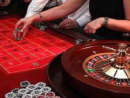 Close up of a hand placing chips on a roulette table, with the wheel in the corner