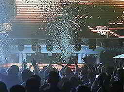A large group of people dancing in a modern nightclub under falling confetti