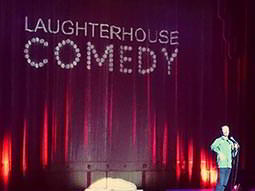 A man performing on stage in front of a purple curtain with the words Laughterhouse Comedy on