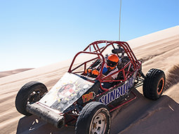 The back of a black off-road buggy racing on a dirt track