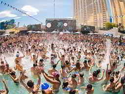 A large group of people dancing in a swimming pool during the day