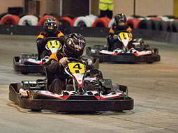 Three people racing in go karts on an indoor track, with tyres lining the track in the background