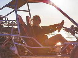 A woman sat in an off-road buggy at sunset