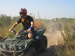 Close up of a man drving a quad bike through a muddy field, with people in the background