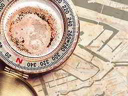 Close up of a compass placed on top of a map