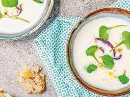 Close up of two white dishes of soup