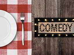 The word Comedy illuminated on a table, with a tablecloth and a plate and fork next to it
