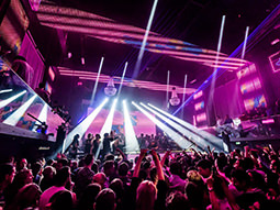 A large crowd in a nightclub that has purple decor and strobe lights