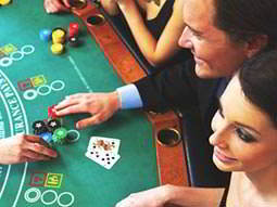 A man and a woman gambling with chips on a poker table