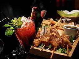 A split image of a red cocktail garnished with a drumstick lolly and a wooden tray of food