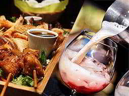 A split image of a wooden box willed with food and a wine glass being filled from a metal cocktail shaker