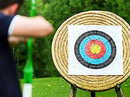 A main aiming a bow and arrow and a wicker archery target
