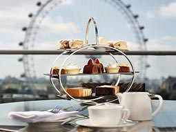A modern cake rack with food on and the London Eye in the background