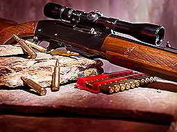 A scoped rifle resting on a surface next to rounds of ammunition