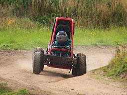 An off-road buggy driving round a corner on a dirt track