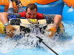 A man lying on his front and holding an inflatable surrounded by water