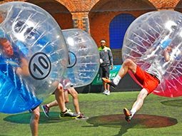Three people in zorbs, running around on a pitch