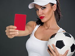 A woman in a white vest and visor, holding a black and white football and a red card in front of her to a grey background