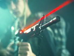 A man aiming a rifle, on which is a laser pointer emitting a visible red laser beam