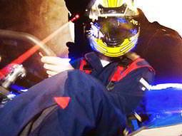 A close up of a person driving a go kart overlaid with a man aiming a laser gun