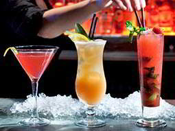Two red cocktails and a yellow cocktail lined up on the bar, with a bartender putting a straw in a cocktail