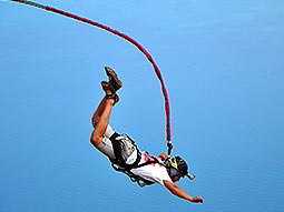 A man, wearing a harness and helmet, falls attached to a bungee cord