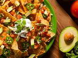 A top-down view of a large plate of nachos and half an avocado
