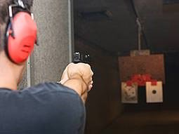 A man aiming a handgun at a target
