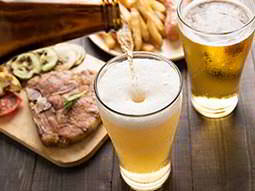 A glass of beer being filled from a bottle, with another glass of beer, a steak meal and a plate of chips