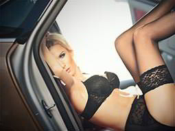 A woman wearing lingerie reclining seductively in a car seat