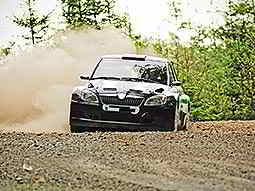A black rally car drifting round a corner on a gravel track