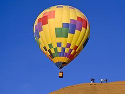 A multicoloured hot air balloon against a blue sky, with people standing nearby