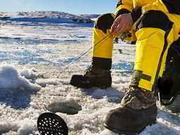 A person wearing a bright yellow snowsuit fishing through a small hole in some ice