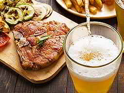 A glass being filled with beer, with a steak meal in the background