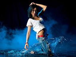 A close up of a woman splashing around in water and crouching down, to a blue smoky backdrop