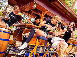Some girls on a beer bike outdoors, drinking beer