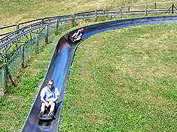 Two men sliding down the toboggan slide outdoors