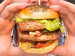 Close up of a mans hand holding a burger to his face