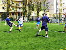 Some men playing football outdoors on a pitch