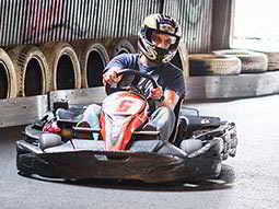 A go kart driving around the track, with lots of tyres in the background