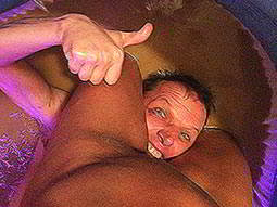 A man holding his thumbs up to the camera, whilst peering out from between a naked, fat womans legs
