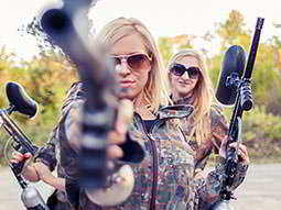 Some girls holding guns and wearing camouflague