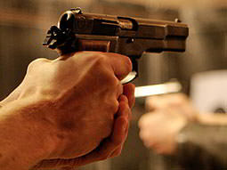 Close up of a mans hands aiming with a pistol