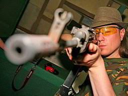 A man aiming with a gun directly towards the camera