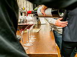 Close up of the back of a waiter pouring a bottle of red wine into glasses