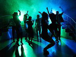 Silhouettes of people dancing in a club, under green and blue disco lighting