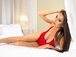A woman wearing red underwear, lying on a bed looking seductive